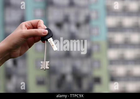 Real estate agent holding house keys on background of new residential building. Concept of house and apartment purchase, rental property - Stock Photo
