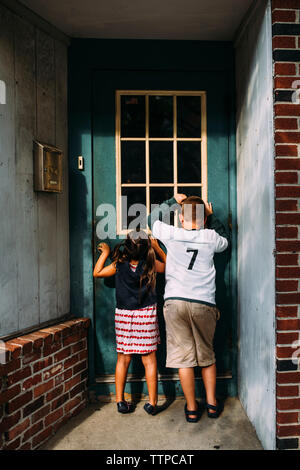 Rear view of playful siblings looking through window at home - Stock Photo