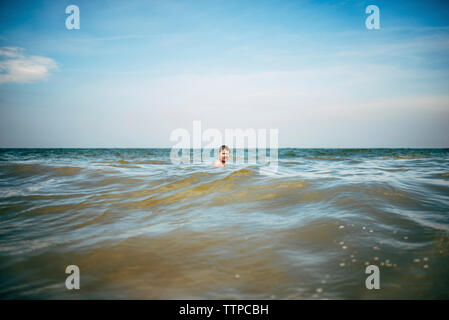 Boy swimming in sea against sky - Stock Photo