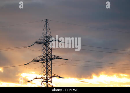 Silhouette of high voltage power line supports with electrical wires on background of evening sky with clouds. Electricity transmission lines