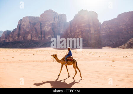 Woman riding on camel in desert - Stock Photo