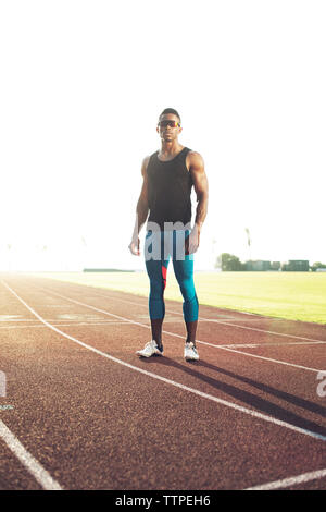 Portrait of confident male athlete standing on running tracks against clear sky - Stock Photo