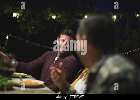 Smiling friends talking while sitting at table during dinner party - Stock Photo