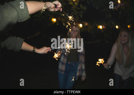Female friends enjoying with sparklers at night - Stock Photo