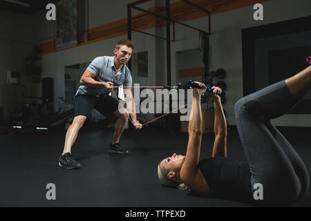 Trainer assisting woman for practicing stretching exercise with resistance band in gym - Stock Photo