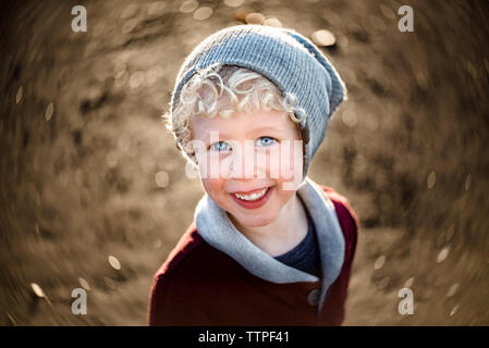 Portrait of happy curly haired toddler wearing a knit hat - Stock Photo