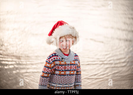 Portrait of happy young boy wearing Santa hat at a beach - Stock Photo