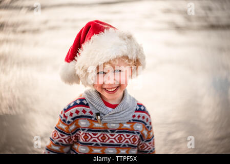 Portrait of cute toddler wearing a Santa hat and sweater - Stock Photo