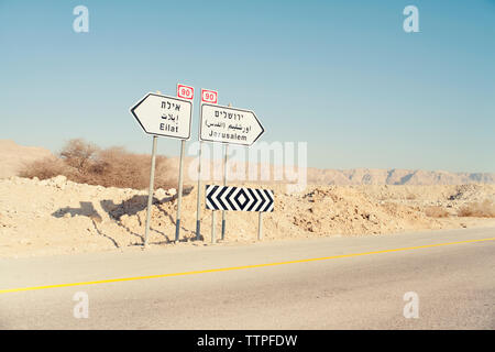 Sign boards on road at desert against clear sky - Stock Photo