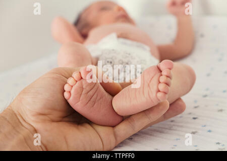 Cropped image of person holding baby's feet on bed - Stock Photo
