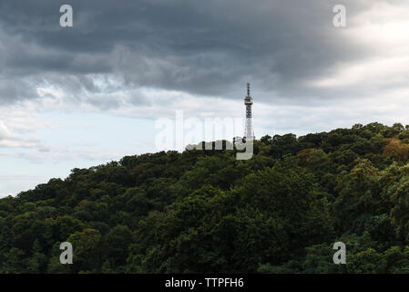 Low angle view of Petrin Lookout Tower on mountain against cloudy sky - Stock Photo