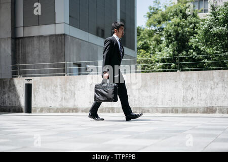 Full length side view of businessman carrying briefcase while walking on bridge in city - Stock Photo
