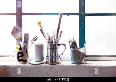 Paint brushes and tools in cup on window sill - Stock Photo