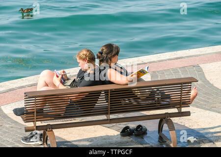 LAZISE, LAKE GARDA, ITALY - SEPTEMBER 2018: Two people relaxing on a wooden bench on the promenade in Lazise on Lake Garda. - Stock Photo