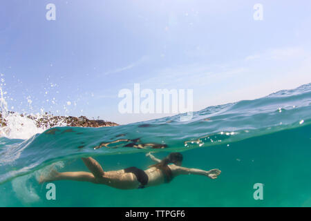 Woman swimming in sea against sky - Stock Photo