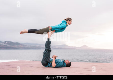 Full length of friends practicing acroyoga on promenade by sea - Stock Photo