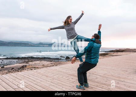 Cheerful friends practicing acroyoga on boardwalk by sea - Stock Photo