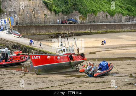 TENBY, PEMBROKESHIRE, WALES - AUGUST 2018: Small fishing boat grounded on sand at low tide in the harbour in Tenby, West Wales. - Stock Photo