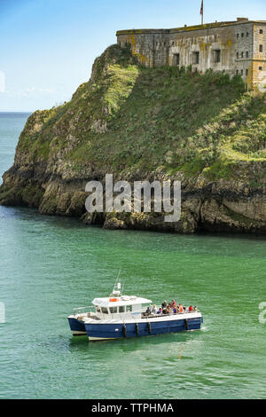 TENBY, PEMBROKESHIRE, WALES - AUGUST 2018: Small harbour trip boat in calm water near the harbour in Tenby, West Wales.