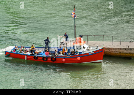 TENBY, PEMBROKESHIRE, WALES - AUGUST 2018: Crew member throwing a line to another person on the jetty as a small harbour tour boat docks in Tenby - Stock Photo