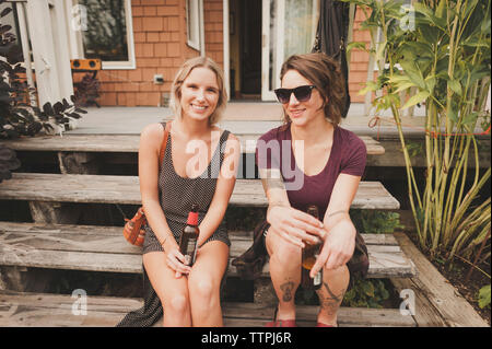Portrait of happy female friends with drinks sitting on wooden steps against house - Stock Photo