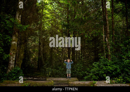 Portrait of boy flexing muscles while standing on log in forest - Stock Photo