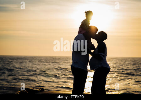 Silhouette man kissing wife while carrying daughter on shoulders at beach during sunset - Stock Photo
