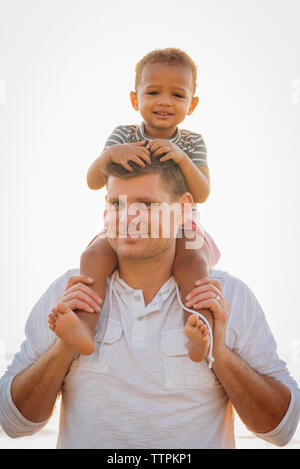 Portrait of father carrying daughter on shoulders while standing at beach against clear sky - Stock Photo