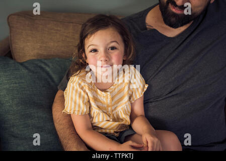 High angle portrait of girl sitting with father on sofa at home - Stock Photo