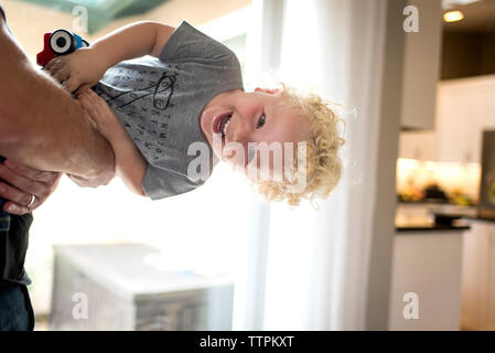 Portrait of cheerful son carried by playful father while playing at home - Stock Photo