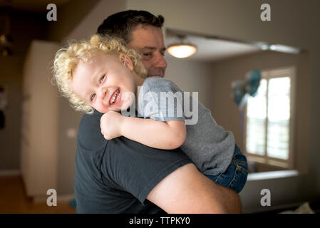 Portrait of smiling son carried by father at home - Stock Photo
