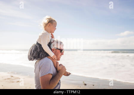 Side view of grandfather carrying granddaughter on shoulders while standing at beach against sky - Stock Photo
