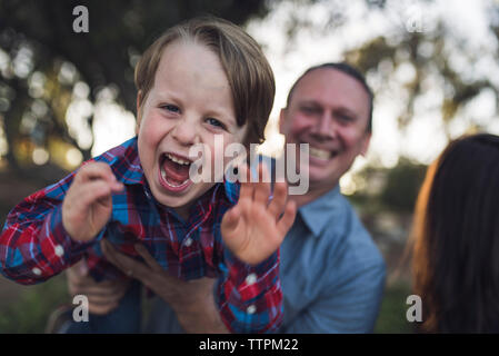 Portrait of playful son carried by father at park - Stock Photo