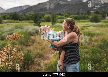 Mother carrying cute happy daughter while standing on grassy landscape against mountains in forest - Stock Photo