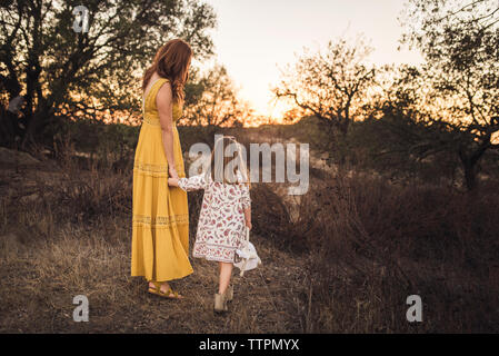 Young girl holding mothers hand while walking away in California field - Stock Photo