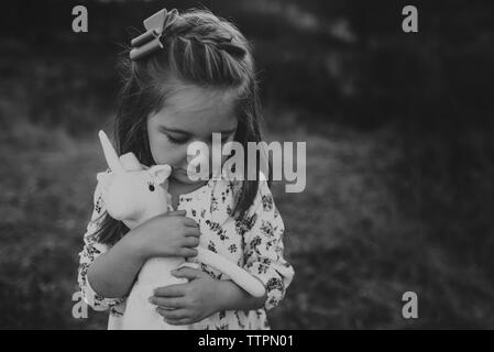 Portrait of young girl holding stuffed animal toy while looking down - Stock Photo