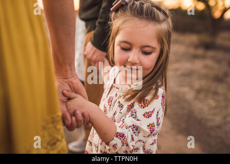 Young girl holding parents hands looking down in California field