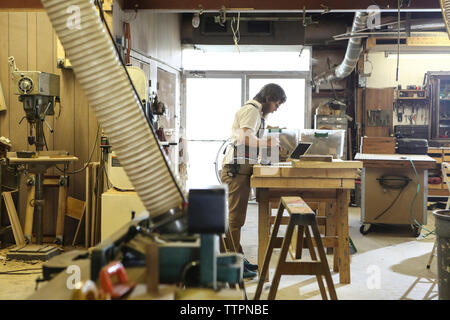 Side view of carpenter examining wooden plank at workbench in workshop - Stock Photo