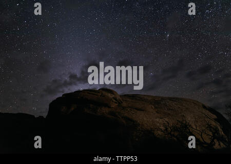 Low angle view of rock formations against star field at night - Stock Photo