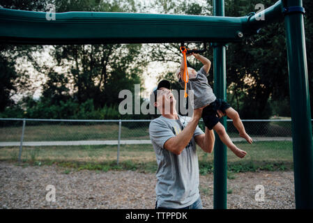 Playful father hanging son on monkey bars at playground - Stock Photo