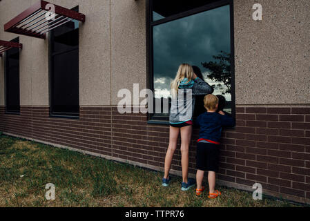 Rear view of siblings peeking through window while standing at backyard - Stock Photo