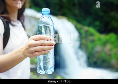 Female tourist holding bottle of clear water on blurred river background - Stock Photo