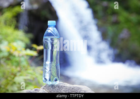 Bottle of clear water on blurred waterfall background - Stock Photo
