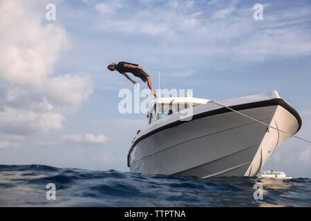 Low angle view of man diving into sea from yacht against cloudy sky - Stock Photo