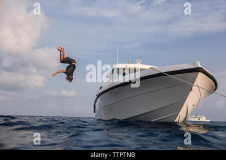 Low angle view of man diving into sea from yacht against cloudy sky at Maldives - Stock Photo
