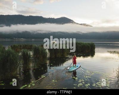 A female paddleboarding on a lake