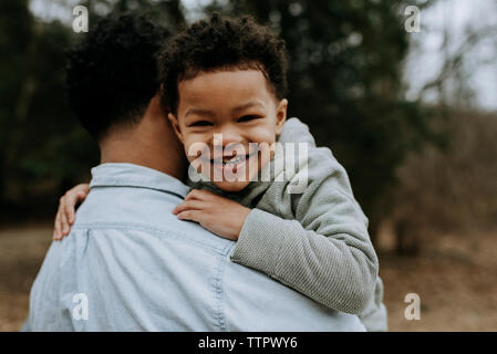 Portrait of happy son being carried by father in forest - Stock Photo