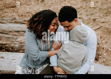 High angle view of couple with son sitting on log in forest - Stock Photo