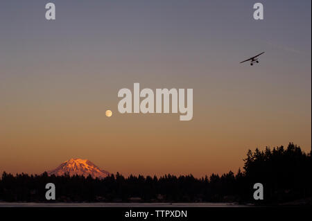 Silhouette airplane flying in clear sky - Stock Photo