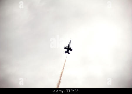 Low angle view of military airplane flying in cloudy sky - Stock Photo